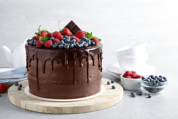 Svježe pripremljena ukusna čokoladna torta ukrašena bobicama na bijelom stolu
