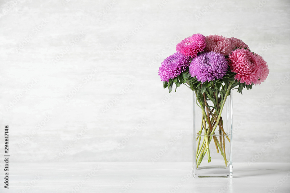 Fototapety, obrazy: Glass vase with beautiful aster flowers on table against light background. Space for text