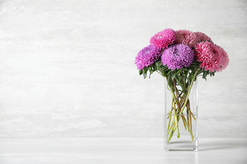 Glass vase with beautiful aster flowers on table against light background. Space for text