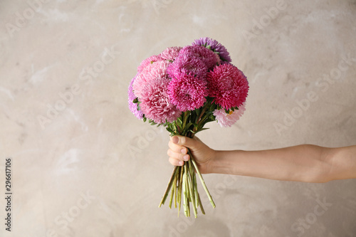 Fotomural Woman holding bouquet of beautiful aster flowers on beige background, closeup