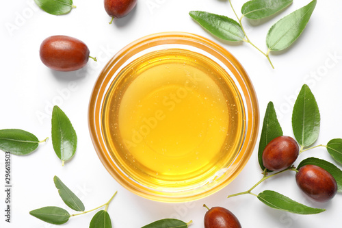 Glass bowl with jojoba oil and seeds on white background, top view Canvas-taulu