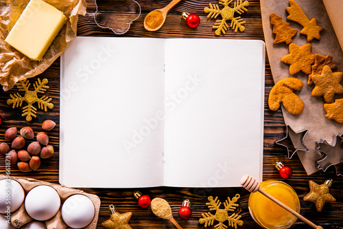Fotografía Traditional christmas holidays pastry ingredients, kitchen utensils and open blank notebook on wood textured table