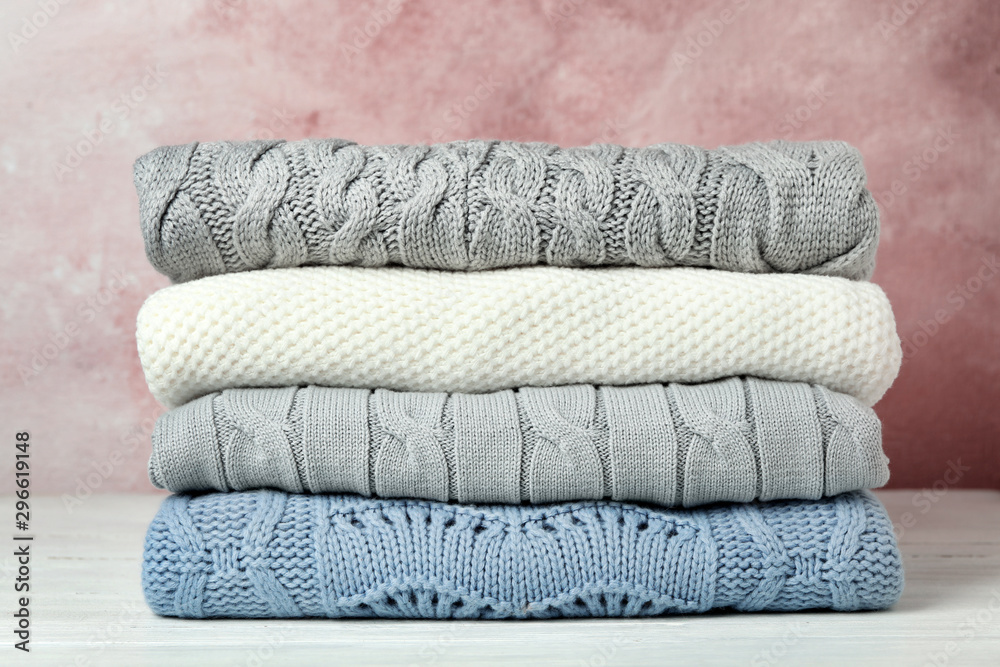 Fototapety, obrazy: Stack of warm clothes on white wooden table against light background. Autumn season
