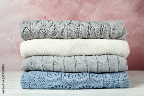 Fotografía  Stack of warm clothes on white wooden table against light background