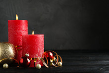 Beautiful Christmas Composition With Burning Red Candles On Black Wooden Table. Space For Text