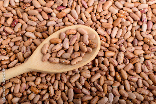 Poster Pays d Europe One wooden spoon in many fresh organic red beans in warm light, top view