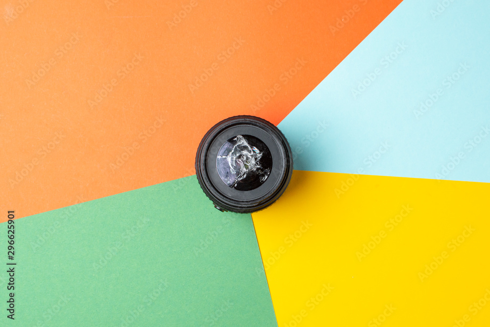 Fototapeta one broken modern photo lens on a colored background, photographic equipment repair concept