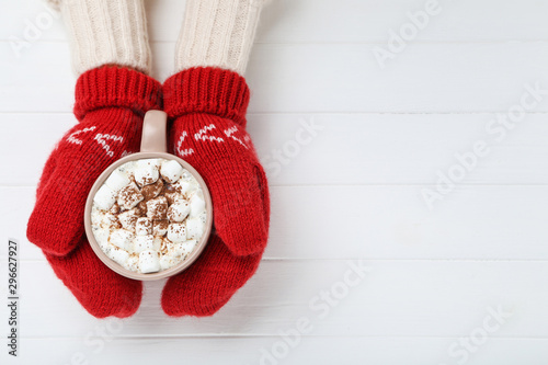 Vászonkép Hands in knitted mittens holding cup of hot drink on white wooden table