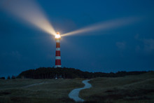 Lighthouse Of Ameland At Night With Light Beaming Across The Deep Blue Sky
