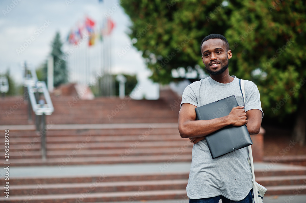 Fototapety, obrazy: African student male posed with backpack and school items on yard of university, against flags of different countries.