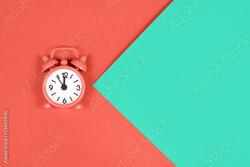 Fotografía Orange alarm clock on colored background.