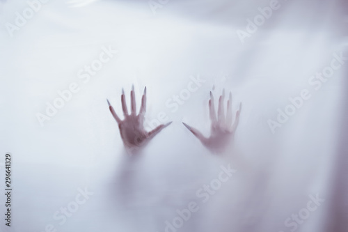 silhouette of a female sexual figure behind foggy glass. concept of the spirit of poltergeist from the other world. frightening hands of death through the fabric. - 296641329