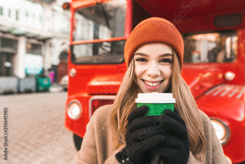 Poster Londres bus rouge Closeup portrait of happy girl with cup of coffee standing against red bus background, looking into camera and smiling. Street photo of cheerful girl on a walk in winter, warmed by warm coffee.