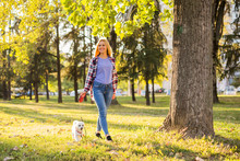 Beautiful Woman Walking With Her Maltese Dog In The Park.