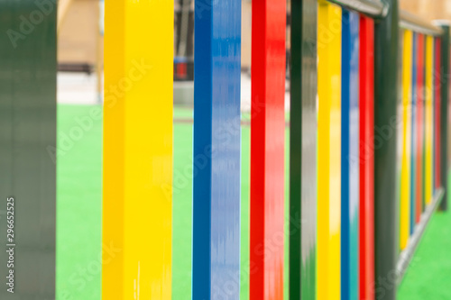 Fototapety, obrazy: Bright multi-colored fence of a playground for children close-up