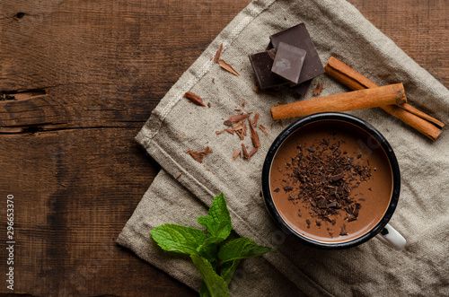Foto auf Leinwand Schokolade cup of hot chocolate, cinnamon sticks, mint and chocolate on wooden table