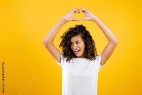Valokuva  happy beautiful black girl showing heart with hands isolated over yellow