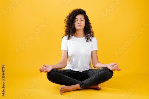 Fotografia relaxed black woman meditating in yoga pose isolated over yellow