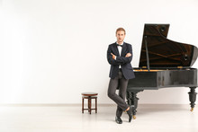 Man Near Grand Piano Against W...