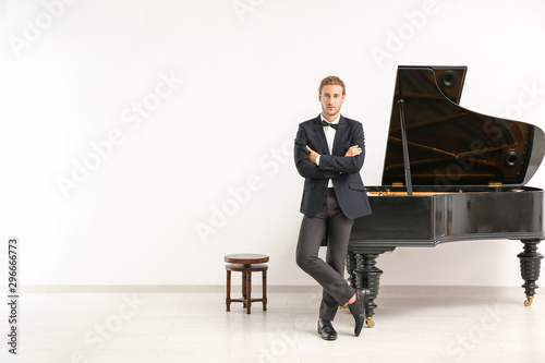 Man near grand piano against white wall Canvas