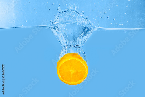 Falling of orange piece into water on light background Tablou Canvas