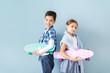 Leinwandbild Motiv Cute fashionable children with skateboards near color wall