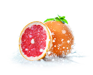 Fresh grapefruit with water splashes on white background