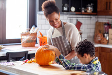 Mother With His Son Prepare Pumpkin For Halloween In The Kitchen