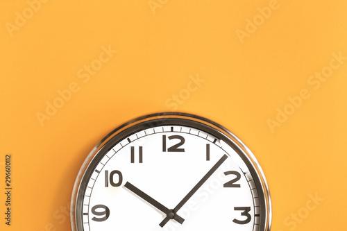 Vászonkép  Part of analogue plain wall clock on trendy pastel orange background