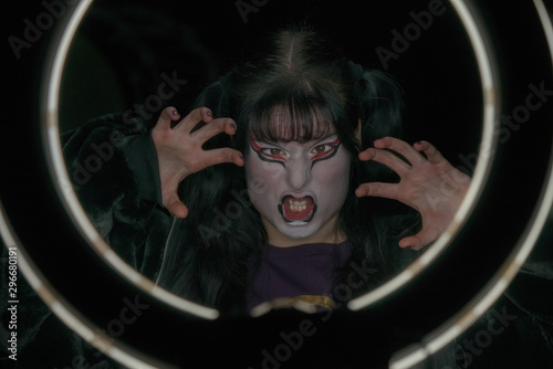Girl with a make-up in the form of a witch or a demon makes a face inside a round frame of light. Halloween pirtrait.