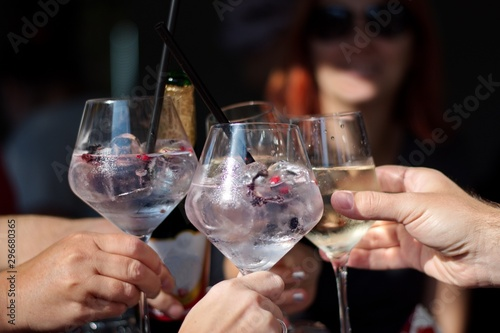Fotomural  Closeup of cocktail in elegant glasses - group of people toasting