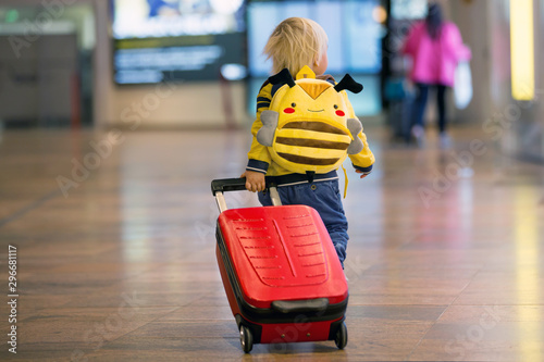 Photo Cute  baby boy waiting boarding to flight in airport transit hall near departure gate