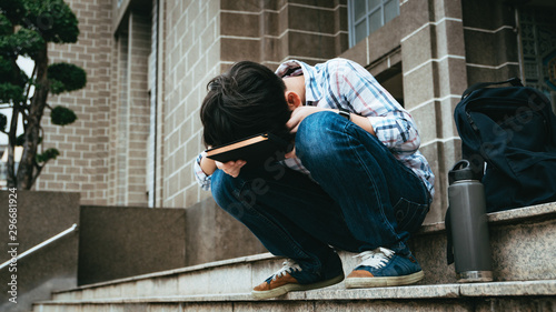 Photo  Good looking teenage Asian boy sit on stairway in front of high school building, bend his face down on notebook, frustrated, overwhelmed as he struggle for exam preparation, heavy homework, workload