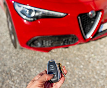 A Hand Operates The Remote Control Of A Beautiful Red Italian Sports Car Alfa Romeo Stelvio