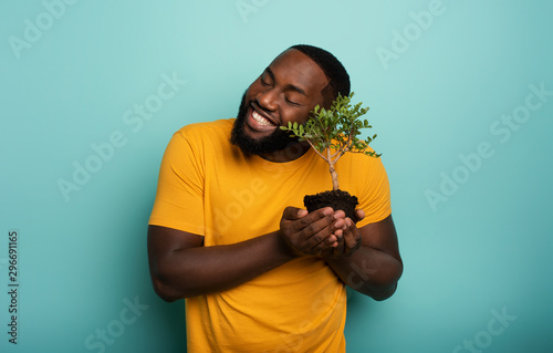 Happy boy loves a small tree ready to be planted Wallpaper Mural