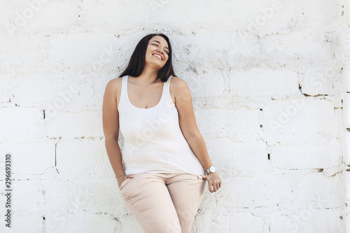 Plus size model dressed in white shirt posing over brick wall Wallpaper Mural