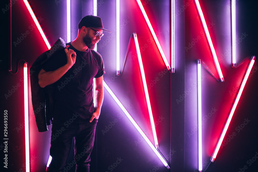 Fototapety, obrazy: Hipster handsome man on the city streets being illuminated by neon signs. He is wearing leather biker jacket or asymmetric zip jacket with black cap, jeans and sunglasses.