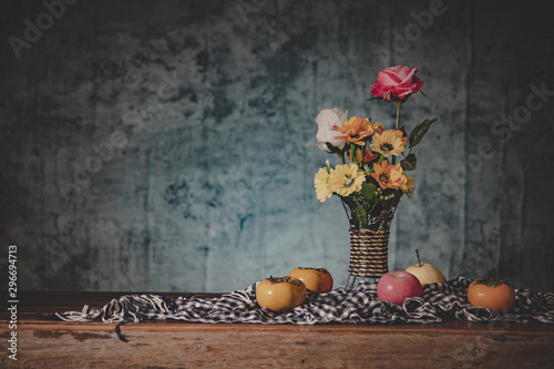Fototapeta Still life with a vase of flowers and fruit placed on a fabric obraz