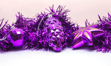 Composition Of Christmas Purple Decorations On A White Surface