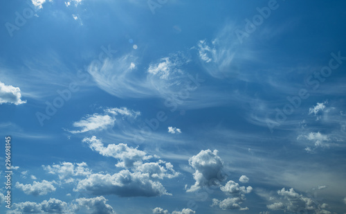 Some light cumuliform and cirrus clouds in the clean blue sky. Fototapeta