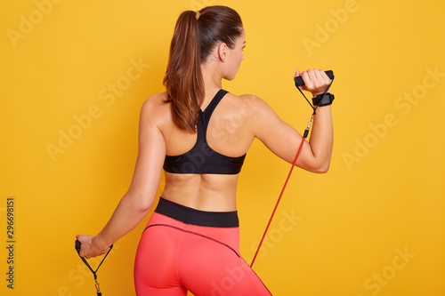 Carta da parati Picture of attarctive sporty woman performs exercising with resistance band, wearing black topand leggins,model posingisolated over yellow background