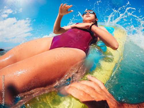 Fototapeta  Girl on the airbed getting splashed by the wave