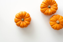 Mini Pumpkins Lay On White Bac...