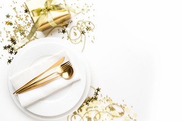 Christmas table setting with dishware, golden silverware on white background. Top view. Xmas