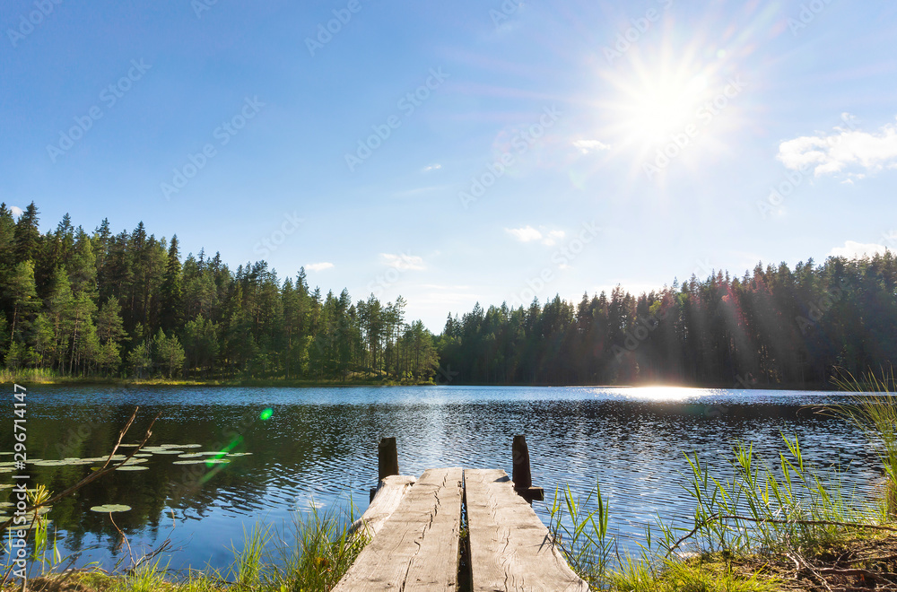 Fototapeta Traditional Finnish and Scandinavian view. Beautiful lake on a summer day and an old rustic wooden dock or pier in Finland. Sun shining on forest and woods in blue sky.