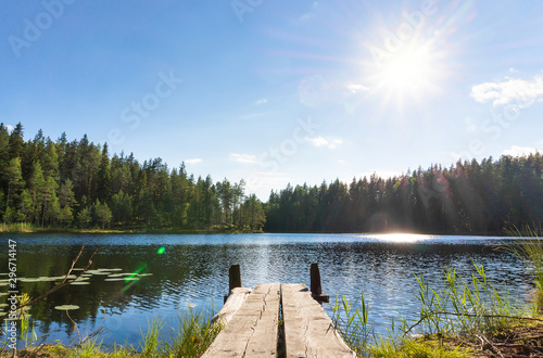 Obraz Traditional Finnish and Scandinavian view. Beautiful lake on a summer day and an old rustic wooden dock or pier in Finland. Sun shining on forest and woods in blue sky. - fototapety do salonu