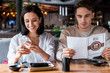 canvas print picture - woman smiling while using smartphone near man with menu