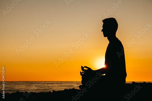 Spoed Fotobehang Ontspanning Silhouette of a man in meditation pose on beach on sea background and sunset. Concept of freedom relaxation. Place for text or advertising