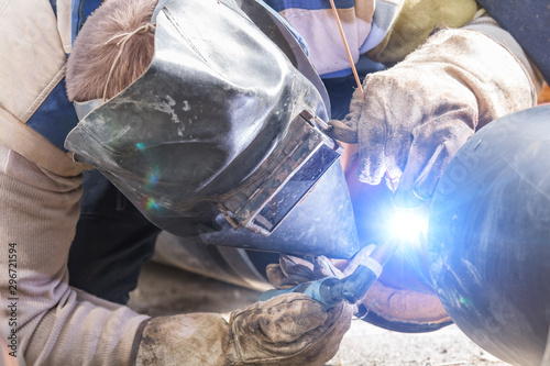 Construction worker welding pipes on a heavy site. Wallpaper Mural