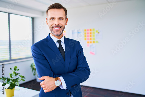 Confident businessman smiling at camera with arms crossed while standing in offi Fototapete
